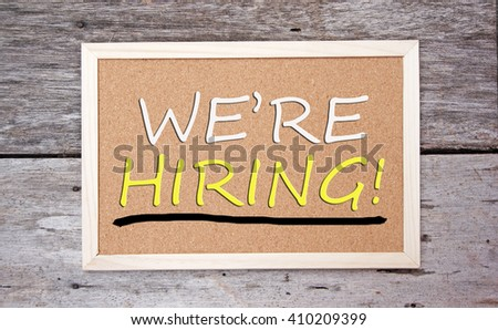 brown board on a wooden table. we're hiring text on the board - stock photo