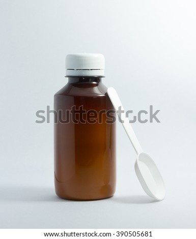 Brown bottle of cough syrup with white plastic spoon isolated on white background - stock photo