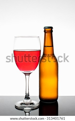 Brown bottle with drops and Glass of beer isolated on a white background - stock photo