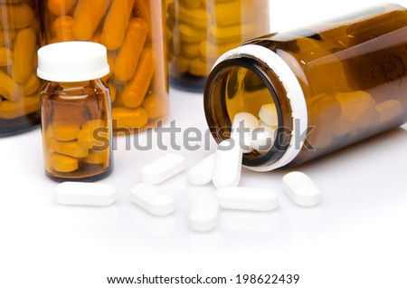 Brown bottles with pills, isolated on white - stock photo