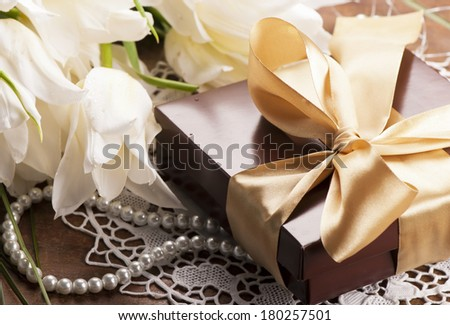 brown box with candies and golden tape  and white tulips