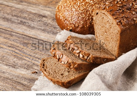 Brown bread on an old wooden table - stock photo
