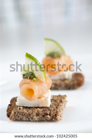 Brown bread salmon appetizer with feta cheese, lime and pesto - stock photo