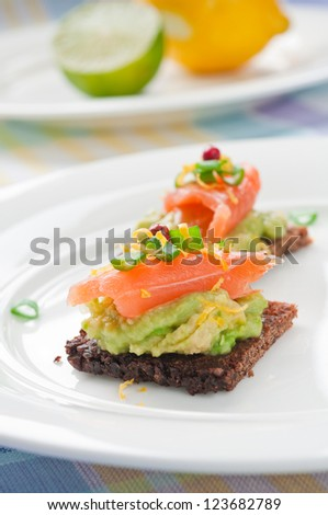 Brown bread sandwich with smoked salmon, avocado topped with chive and pepper - stock photo