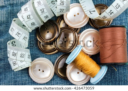 Brown Buttons and Sewing Accessories on Denim Background. - stock photo