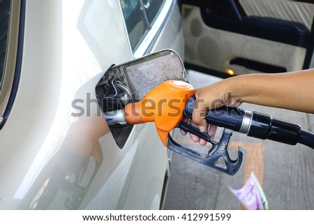 Brown car with Orange Fuel nozzle on a gas station.