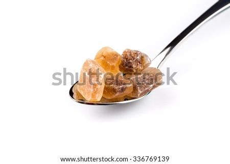 brown caramelized sugar in a wooden spoon on a white background