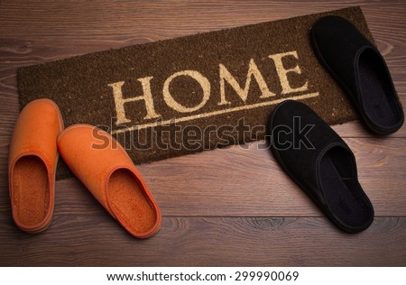 Brown carpet doormat with text Home and slippers - stock photo