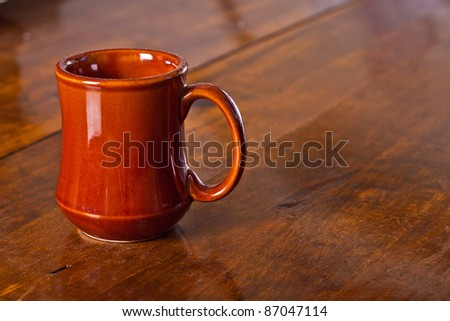 Brown ceramic coffee mug sitting on a wooden surface - stock photo
