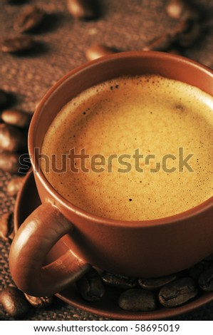 Brown ceramic cup of coffee with froth close-up and roasted coffee beans on brown canvas. - stock photo