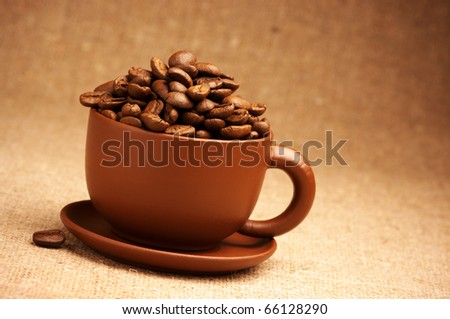 Brown ceramic cup with roasted coffee beans on canvas.