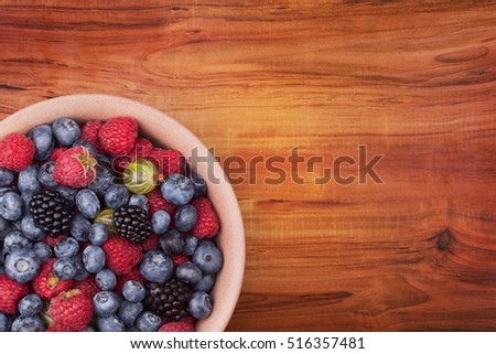 Brown ceramic plate with berries on the left bottom corner of the wooden table with clipping path. Top view.