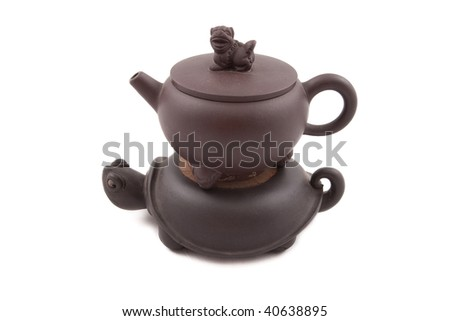brown ceramic teapot with turtle-shaped stand isolated on white