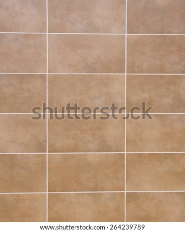 Brown ceramic tiles with white fugue on wall closeup  - stock photo