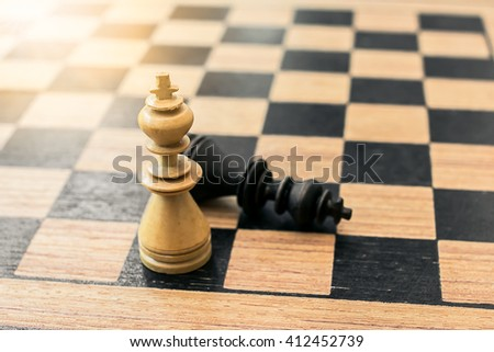 Brown chess king stand on the chessboard, while black chess king laying down - stock photo