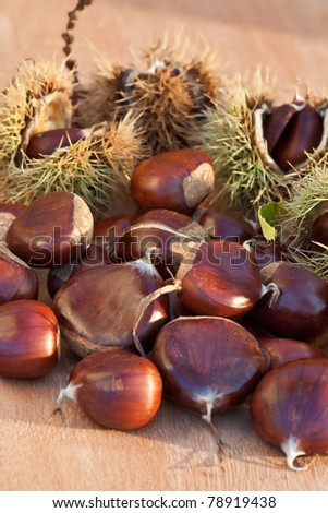 Brown chestnuts on a wooden desk. - stock photo