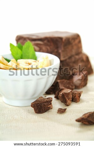 Brown chocolate chunk block and fresh cut bananas. This is perfect harmony of tasting flavor chocolate and banana for cake, muffin, ice cream, fondue, pie, yogurt and your favorite desserts. - stock photo