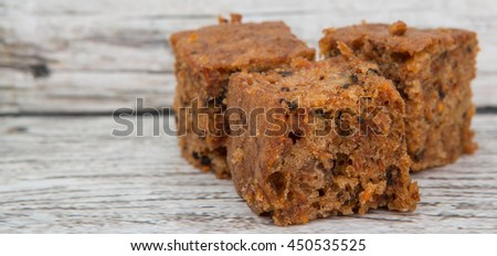 Brown chocolate flavored carrot cake over wooden background