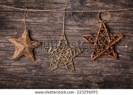 Brown christmas decorations attached to the rope, over wooden background - stock photo