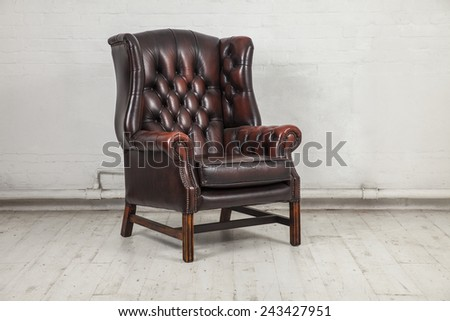brown classic chair in dusty warehouse space - stock photo