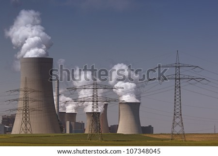 Brown coal power plant with huge cooling towers and steam and powerlines - stock photo