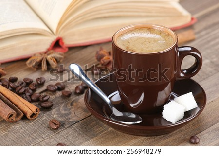 brown coffee cup in a saucer on the background of wooden planks - stock photo