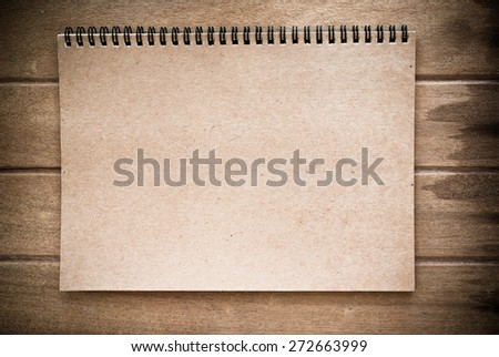 Brown color notebook on wood background, vintage tone - stock photo