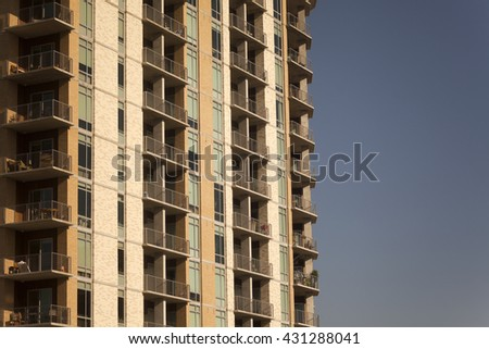 Brown colored residential high-rise building with balconies against a clear blue sky - stock photo