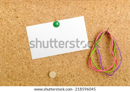 Brown Cork Board with Tacks, Index card and Rubber Bands - stock photo
