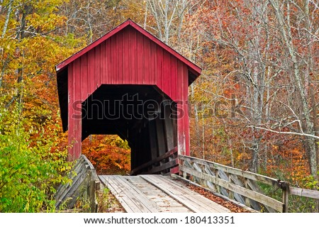 Brown County Indiana's Bean Blossom Covered Bridge, built in 1880 and seen here surrounded by colorful fall foliage, is a very rare example of a Howe single truss structure. - stock photo