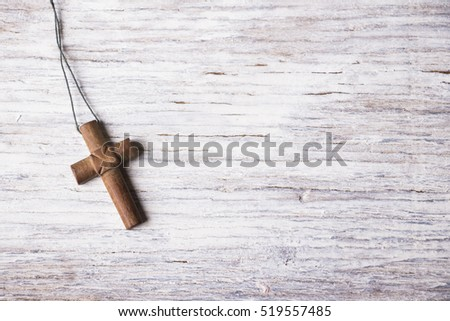 Brown cross on a white wooden background
