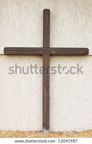 Brown cross on white wall - stock photo