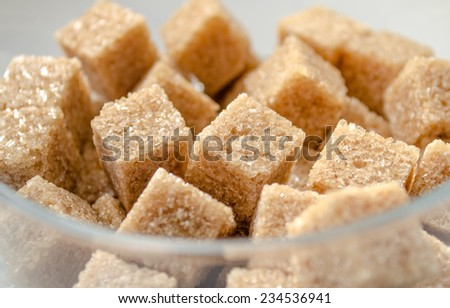 Brown cubes of cane sugar in the glass cup .