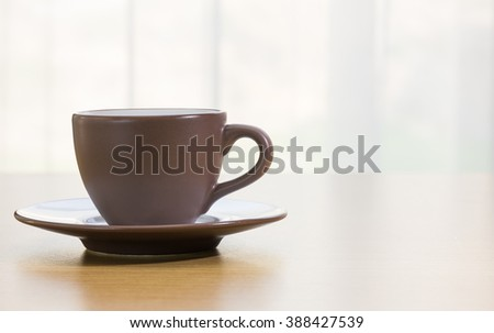 Brown cup of coffee on wood table - stock photo