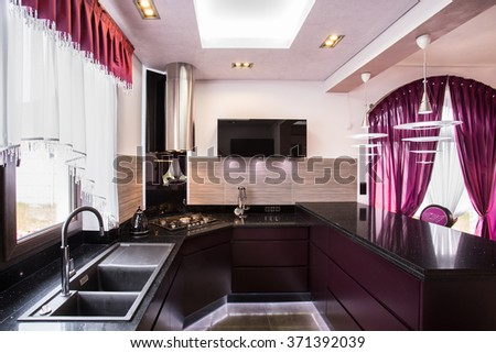 Brown cupboards and worktops in luxury kitchen - stock photo