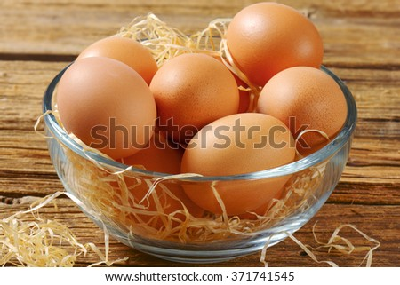 Brown eggs in a glass bowl on wooden background