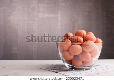 brown eggs in a large glass bowl on a light wooden table and a side view - stock photo