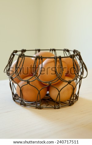 Brown eggs in a wire basket in natural light - stock photo