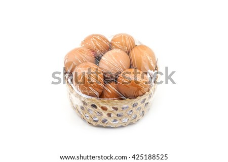 brown eggs in bamboo basket with plastic wrap - stock photo