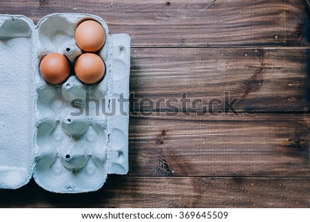 Brown eggs in box on wood table - stock photo