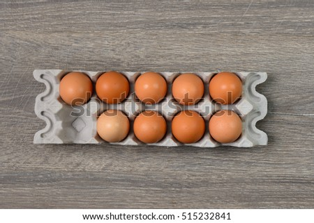 Brown eggs in separate tray on wooden table
