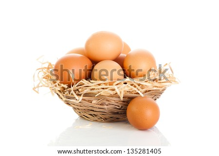 Brown eggs in the basket on white. - stock photo