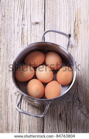 Brown eggs in water in a pan - stock photo