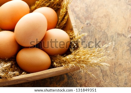 Brown eggs in wooden square bowl - stock photo
