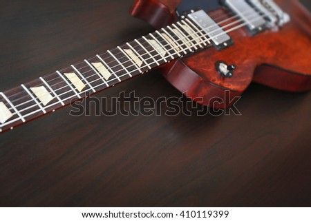 Brown electric guitar on black wooden background - stock photo