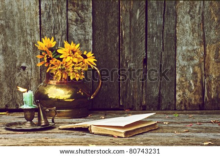 Brown eyed Susan flowers in an antique copper vase and an old book,  and antique candle holder on a rustic wood backdrop with copy space.