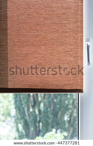 Brown Fabric Blinds On A White Plastic Window