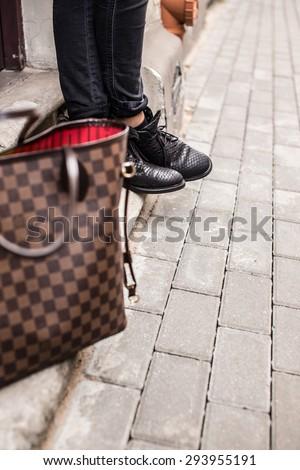 Brown fashinable bag and black woman's boots. - stock photo