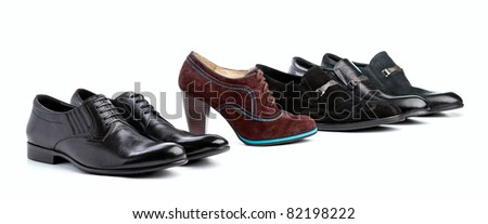 Brown female boot between black male shoes in range - stock photo