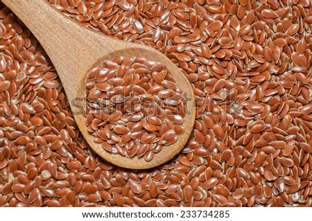 Brown flax seeds. Flax / Linseed (Linum usitatissimum) in wooden spoon. Vegetarian / vegan food. - stock photo